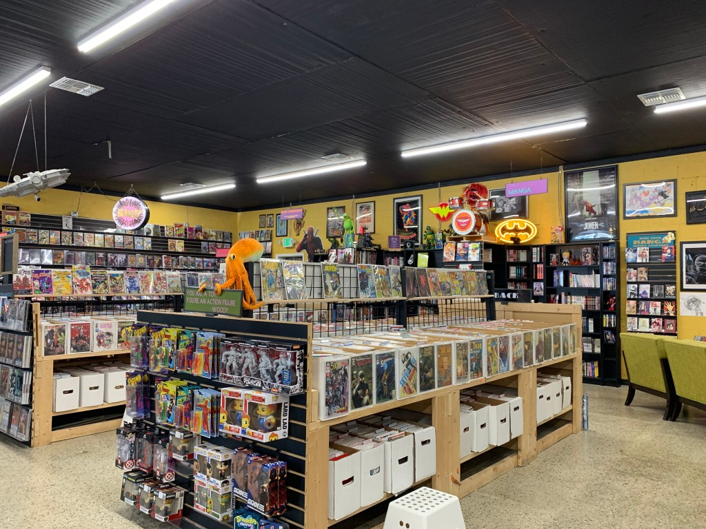 A view of the interior of BAMF Comics & Coffeehouse. The walls are fulled to bursting with comic book heroes and logos on framed posters and neon signs. The shelves are stocked with comics and graphic novels, action figures, stuffed animals and an assortment of collectables.