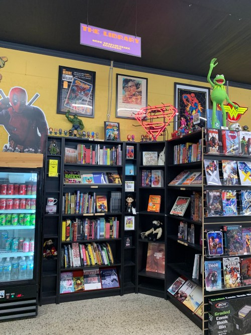 The Library, a portion of BAMF Comics containing books and novels of various genres. Also pictured is a fridge filled with several sodas and fresh water. And of course, a cut out of Deadpool, because no comic shop is complete without a Mere with a Mouth!