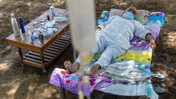 A Covid-19 patient receives treatment at a makeshift open-air clinic in Mewla village, UP, India.