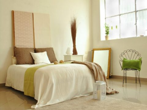 letto matrimoniale con lenzuola bianche e coperta verde acido, specchio a terra e sedia in metallo