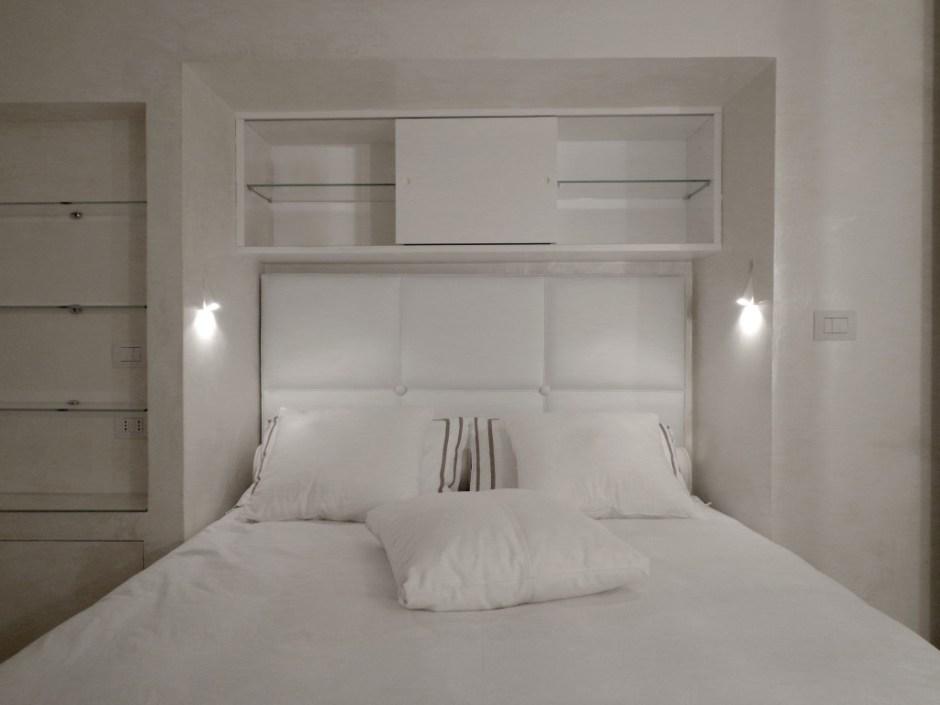 camera da letto total white con arredi su misura e applique a parete