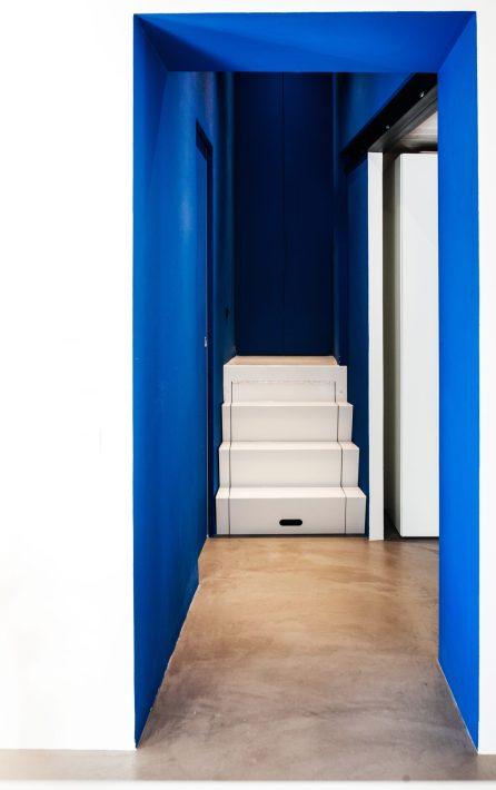 Corridoio con pareti blu elettrico che danno su piccola scala a cassetti e pavimento in cemento
