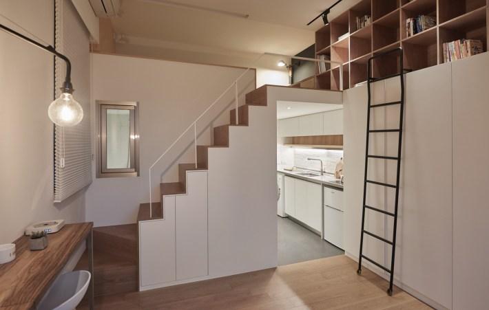 Monolocale a doppia altezza con scala attrezzata ad armadio che porta alla zona notte e libreria.