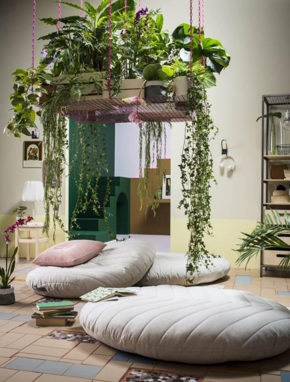 Cuscini pouf tondi sotto porta piante in metallo ancorato a soffitto.