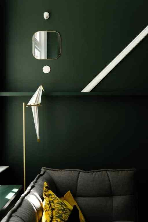 Dettaglio di un soggiorno con pareti verde scuro, angolo di divano in tessuto grigio e cuscino giallo.