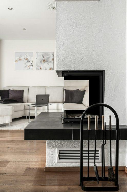 Dettaglio di un camino in muratura contemporaneo che da su un divano ad angolo bianco con cuscini in velluto grigio.