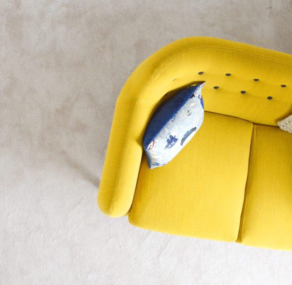 Vista dall'alto dell'angolo di un divano a due posti giallo con cuscino in stile marino.