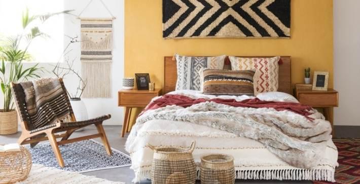 Camera da letto in stile etnico con tessuti naturali e accessori in differenti pattern e in colori caldi.