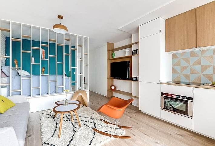 Cucina lineare laccata bianca con pensili in essenza collegata con parete soggiorno, in un piccolo monolocale con elemento divisorio freestanding tra divano e letto.