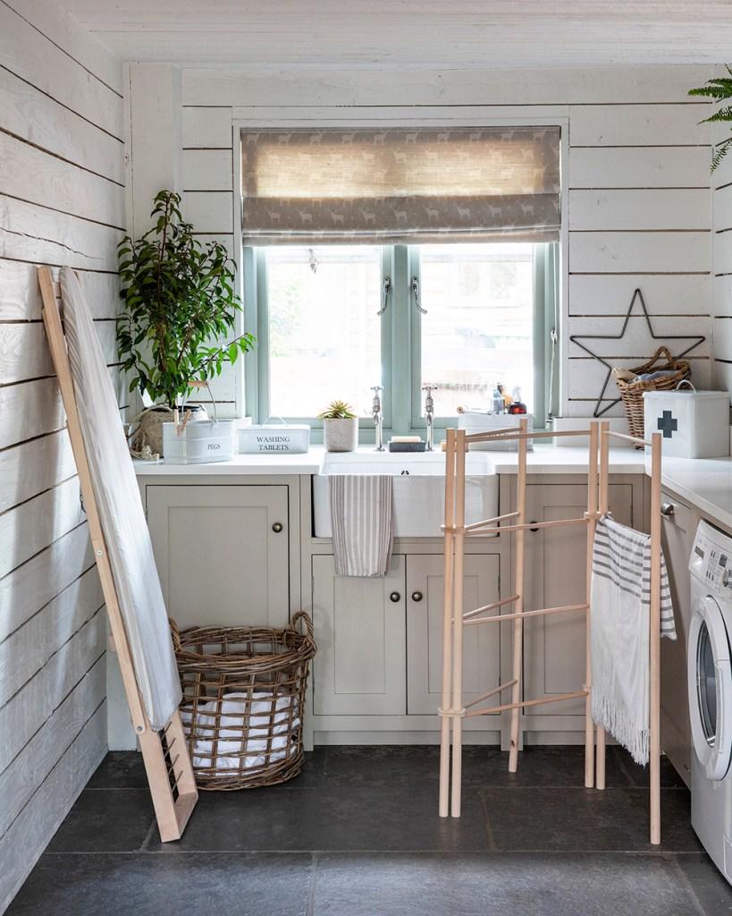 Lavanderia in casa in cucina con scala porta biancheria, stendi panni in legno e cucian rustica color tortora