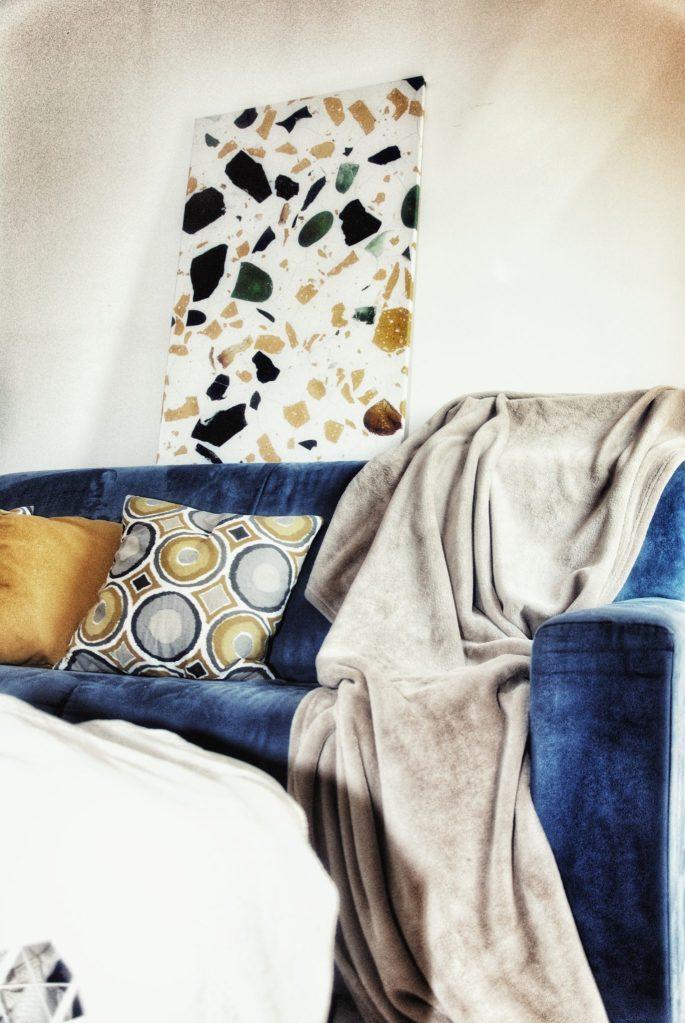 Soggiorno con divano blu e quadro moderno a tema terrazzo