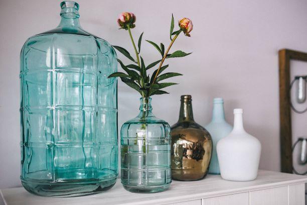 bottiglie azzurre in vetro e in ceramica su credenza bianca