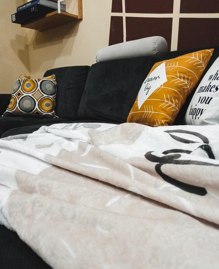 divano grigio scuro su parete beige e marrone, con cuscino senape e grigio