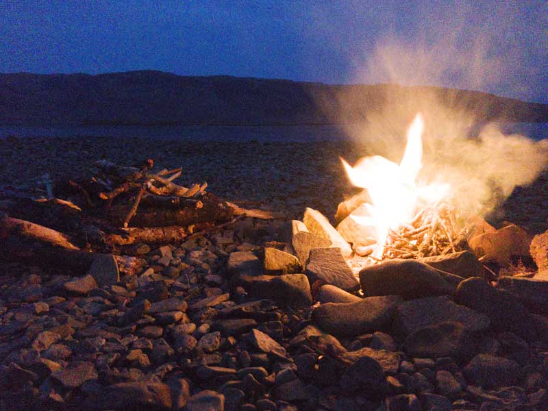 ending the day relaxing around a driftwood beach fire