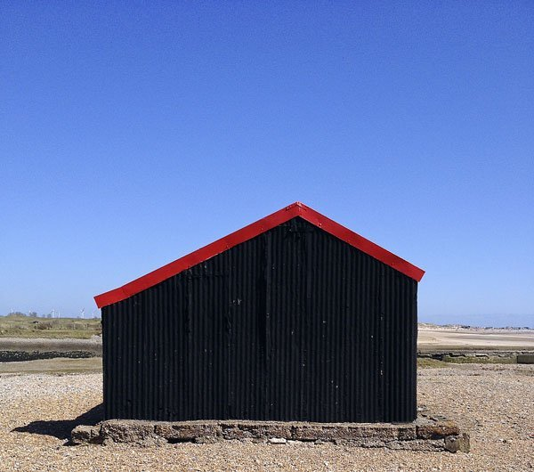 Red and black corrugated metal hut points to the sky