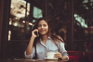 Young woman talking on the phone while sitting at a restaurant drinking coffee, asking about moving services NJ.
