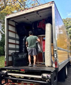 A man standing in a big moving truck full of packages
