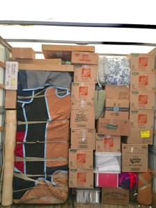 Moving truck loaded to the very top with packed moving boxes and supplies.