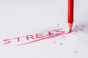 A pencil writing down the word stress.