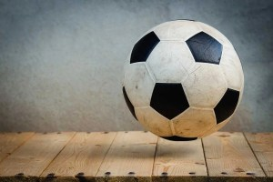 A black and white soccer ball on above a wooden surface, white background