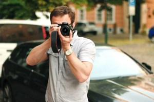 A man holding a camera, cars and a building in the background