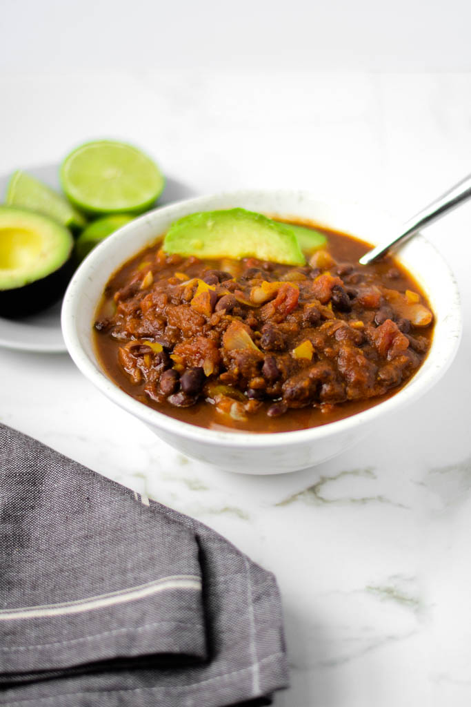 This spicy black bean vegan chili tastes so delicious and is so simple to make! Just toss everything in your slow cooker and enjoy. #chili #chilirecipe #recipe #recipeoftheday #recipeidea #veganrecipes #veganfood