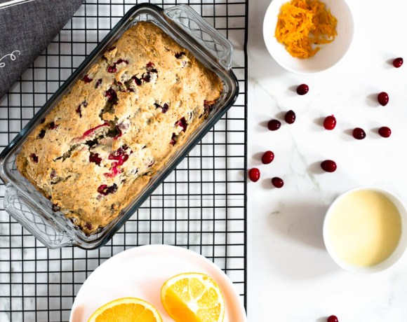 This vegan cranberry orange bread with glaze tastes so delicious and moist! It's quick and simple to make and ready quick. Pin it, you're gonna love it! #cranberryorangebread #vegancranberryorangebread #easycranberryorangebread