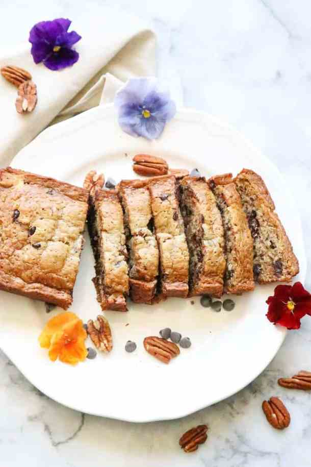 Top View of Sliced Banana Bread with Pecans and Chocolate Chips surrounding.