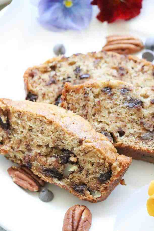 Vertical view of Sliced Banana Bread with pecans and chocolate Chips on a plate.