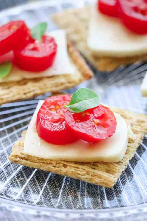 Sliced Vegan Mozzarella Cheese sliced on crackers and topped with tomato slices and a basil leaf.