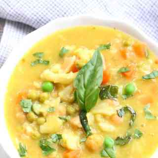 Overhead view of Chickpea and Cauliflower Curry in white bowl with garnish of fresh basil.