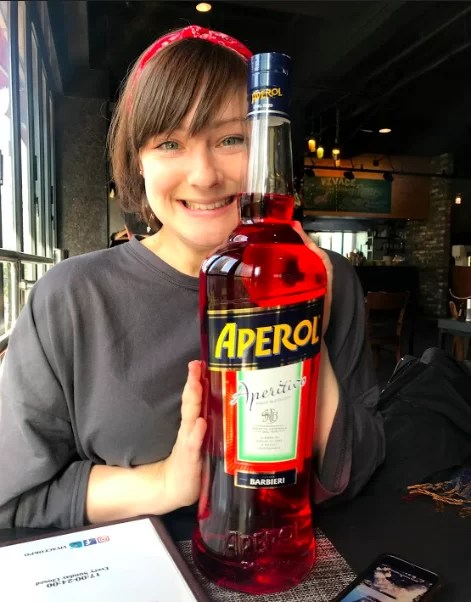 One of the vegan sisters, Alice, whilst living in South Korea - with a BIG bottle of Aperol