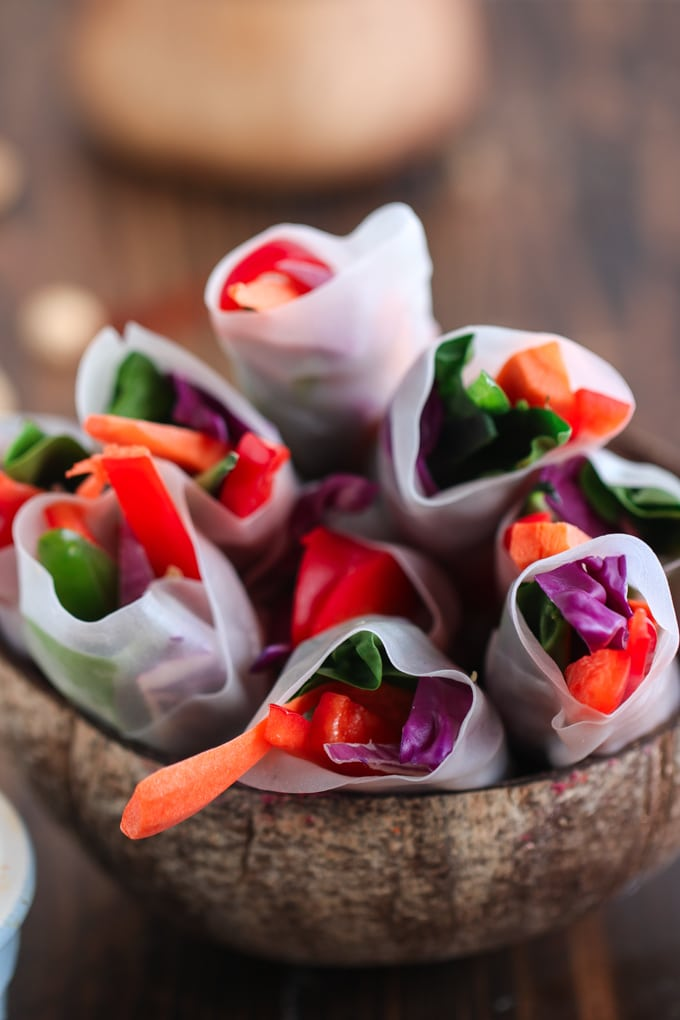 Closeup picture of vegan spring rolls in coconut bowl on wooden table