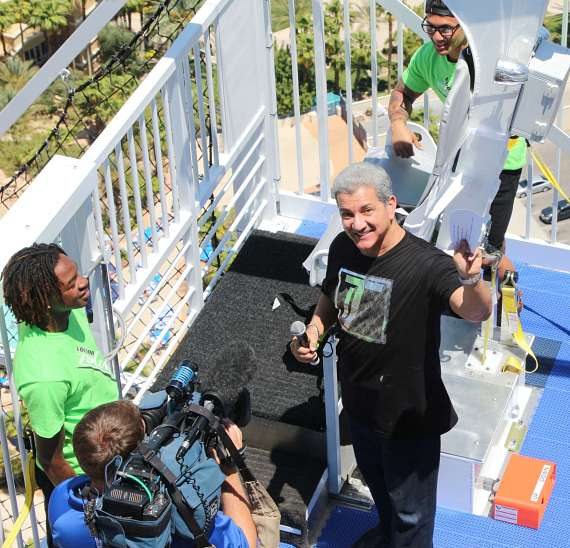 Bruce Buffer, with microphone, prepares to take a seat in the new VooDoo Zip Line ride