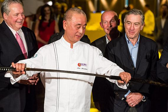Chef Nobu Matsuhisa brings out a sword for the ribbon-cutting ceremony