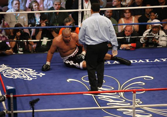 Jameel McCline on the canvas as referee Tony Weeks picks up the count