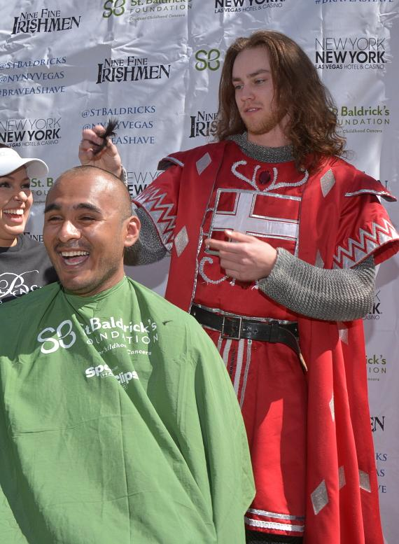 A cast member from Tournament of Kings shaves a participant at seventh annual St. Baldrick's Day head-shaving event