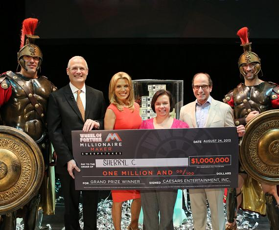Accompanied by Caesars centurions, (left to right) Gary Selesner, Vanna White and Harry Friedman present Sherryl C with a $1 Million check