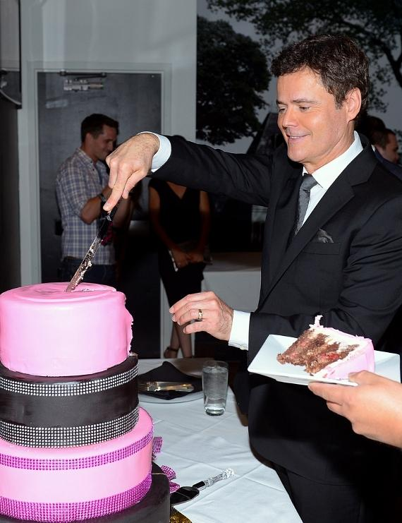 Donny Osmond slices cake that celebrates the 1000th performance of the Donny & Marie show at the Flamingo Las Vegas