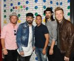 Backstreet Boys pose in front of candy dot wall