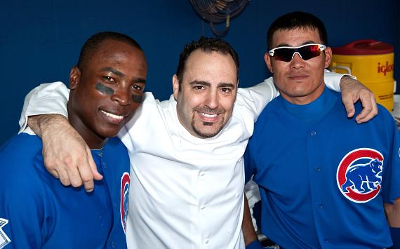Outfielders for the Chicago Cubs, Alfonso Soriano and Kosuke Fukudome, pose with Chef Barry in the dugout during pre-game festivities