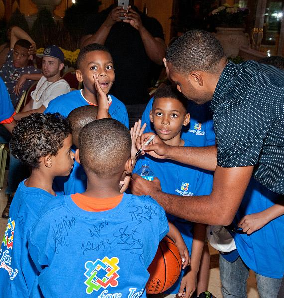 Eric Gordon signs shirts for kids from the Jump For Joy Foundation