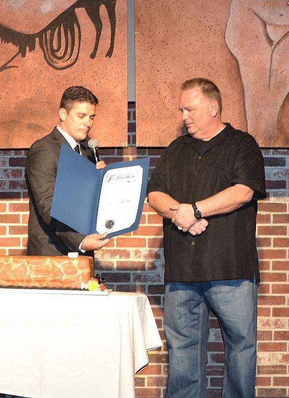 """Damian Costa, regional director of entertainment operations at Caesars Entertainment, presents Kevin Burke with a proclamation, signed by Mayor Carolyn G. Goodman naming Monday, May 13, 2013 as """"Kevin Burke Day"""" in Las Vegas in recognition of his work as Defending the Caveman's leading caveman for 10 years."""
