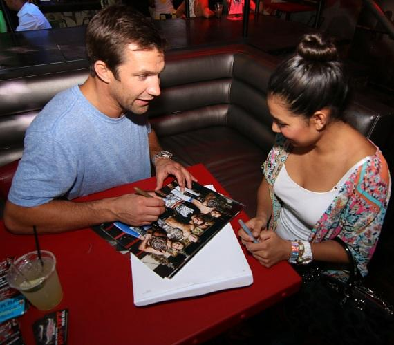 Luke Rockhold autographs his poster for a fan