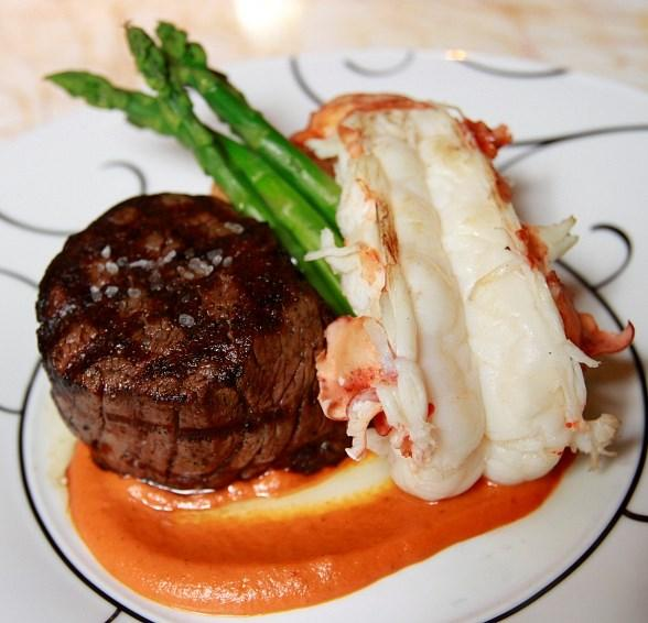 Surf and turf featuring filet mignon and a butter-poached lobster with a lobster croquette and asparagus