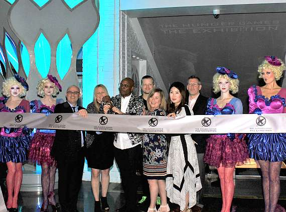 Ribbon cutting with Mark Kemper, Jenefer Brown, Welby Altidor, Elden Henson, Kirsten Taylor-Hall, Zoe Tan and Jeff Segan flanked by models dressed as the character Effie Trinket from The Hunger Games movie franchise