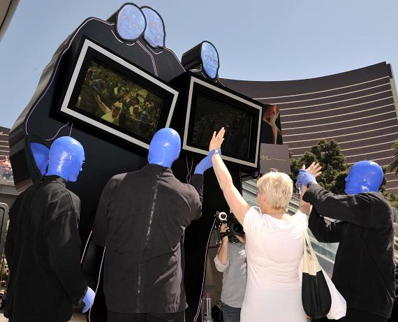 The Blue Men interact with audience members and the statue