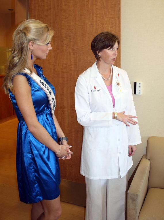 Dr. Karen Milligan and Miss USA discussing treatment in an NVCI exam room.