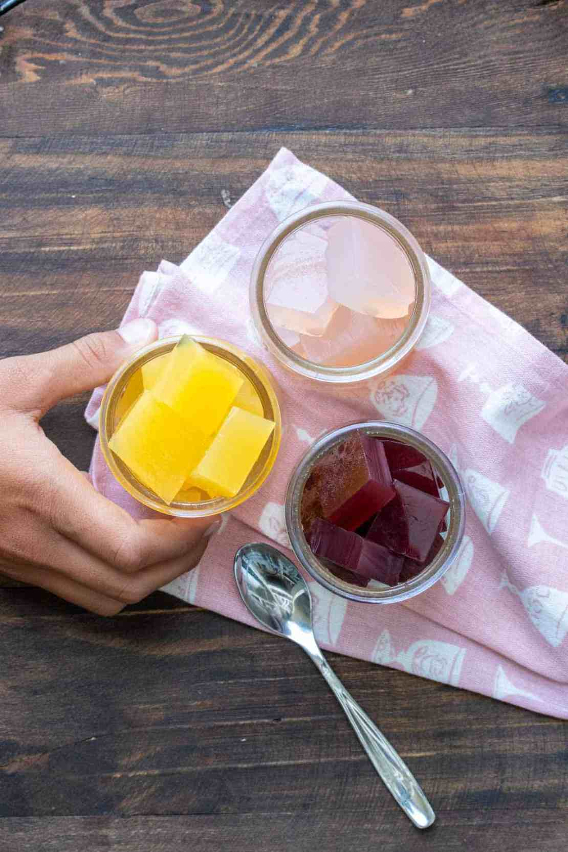 Three glass jars filled with different flavored jello cubes on a pink napkin