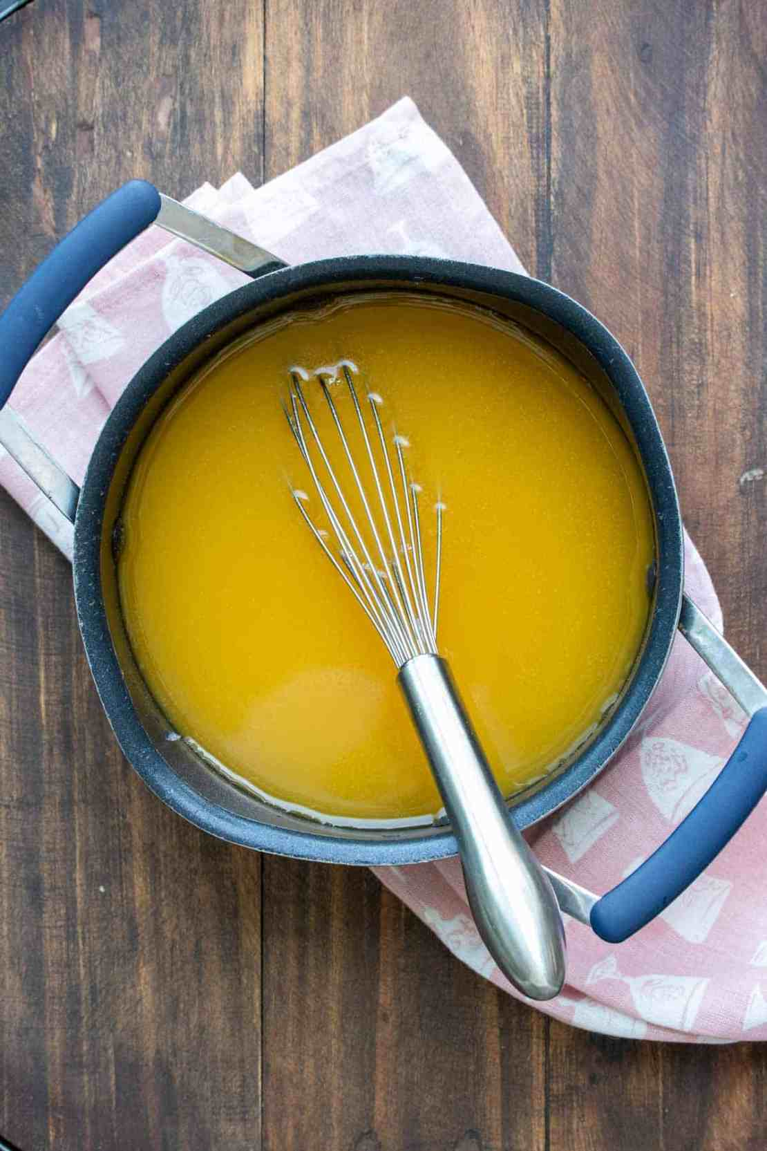 Whisk mixing an orange liquid in a black pot on a wooden surface